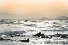 Hypnotisierende seidige Wellen in der Dämmerung, die auf Felsen spritzt Lizenzfreie Stockfotografie