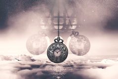 Hypnotising watch on a chain swinging above clouds Royalty Free Stock Photos