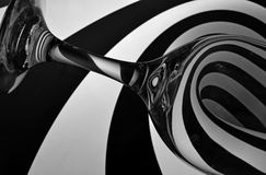 Hypnotizing wine glass. Black and white photo of a clear wine glass against spiraling black and white background Stock Images