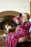 Hypochondria. Mature woman dressed in flannel pajamas sitting in a chair in front of a fireplace in the home wearing a neck brace, blood pressure cuff, arm Royalty Free Stock Photos