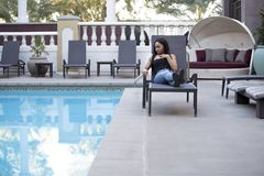 Hypochondriac Female Tourist Disgusted at Pool. Hypochondriac or germaphobe black female on a vacation in a hotel resort looking disgusted at the public swimming Stock Image