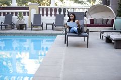 Hypochondriac Female Tourist Disgusted at Pool. Hypochondriac or germaphobe black female on a vacation in a hotel resort looking disgusted at the public swimming Stock Photo