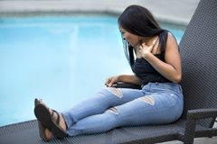 Hypochondriac Female Tourist Disgusted at Pool. Hypochondriac or germaphobe black female on a vacation in a hotel resort looking disgusted at the public swimming royalty free stock images