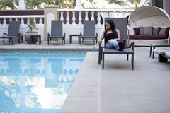 Hypochondriac Female Tourist Disgusted at Pool. Hypochondriac or germaphobe black female on a vacation in a hotel resort looking disgusted at the public swimming royalty free stock photos