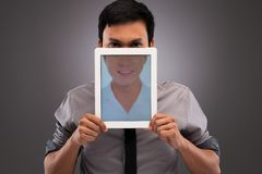 Hypocrisy in the internet. Portrait of evil man with half of his face covered by digital tablet with an image on happy smile: hypocrisy in the internet concept Royalty Free Stock Photography