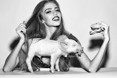 Hypocrisy and pretense. Woman with burger and pigglet Stock Photography