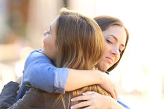 Hypocritical girl embracing a friend. Outdoors in the street Royalty Free Stock Images