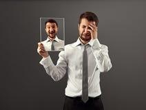Man hiding his gladness. Hypocritical man hiding his gladness Royalty Free Stock Photos