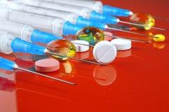 hypodermatisk injektionsspruta Injektionssprutor med blåa visare på en röd bakgrund Medicinska insprutningspumpar Royaltyfri Foto
