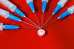 hypodermatisk injektionsspruta Injektionssprutor med blåa visare på en röd bakgrund Medicinska insprutningspumpar Royaltyfri Bild