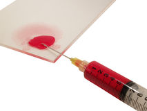 Hypodermic. Needle with blood spilling onto a glass slide royalty free stock image