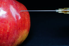 Hypodermic Needle Injecting a Red Apple Stock Image