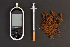 Hypoglycemia concept with glaucometer insulin syringe and brown. Hypoglycemia concept with glaucometer insulin syringe and healthy natural brown sugar pile stock image