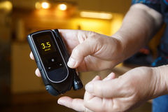 Hypoglycemic diabetic patient testing her sugar level. Hypoglycemic diabetic patient testing her blood for sugar level at home; low blood sugar. Medical process Stock Images
