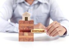 Hypothèque de mot de prise d'homme d'affaires sur le puzzle avec le modèle à la maison en bois Images stock