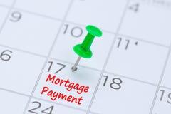 Hypotheekbetaling op een kalender met een groene duwspeld die wordt geschreven aan Royalty-vrije Stock Fotografie