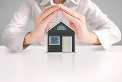Hypotheekconcept door huis van hand Stock Foto