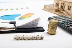 HYPOTHEEKwoord op houtsnede, gouden muntstukken en clipbord met grafiek, modelhuis wordt geschreven dat Stock Afbeeldingen