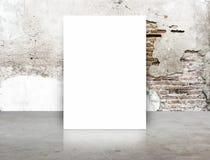 Hyr rum den tomma affischen för vit i sprickategelstenvägg och betonggolvet, T royaltyfri bild