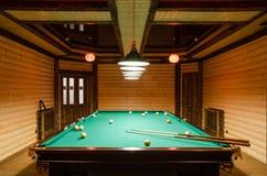 Hyra rum biljard som dekoreras i mörkt trä med låga lampor, billiardtabell med den gröna torkduken royaltyfri foto