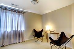 Hyra rum hörnet med två moderna stolar och tabell Arkivbild