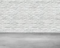 Hyra rum inre med den vita tegelstenväggen och betonggolvet Arkivfoto