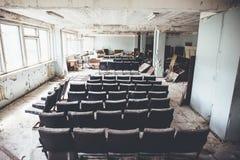 Hyra rum med raws av stolar i den övergav och fördärvade industriella fabriken, kuslig åldrig byggnad efter krig, inga personer royaltyfri fotografi