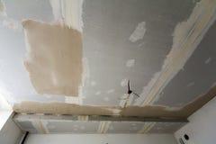 Hyra rum under reparation eller byggnad av det nya huset eller apartementen Inställt grovt vitt tak av drywallen inte färdigt med Arkivbild