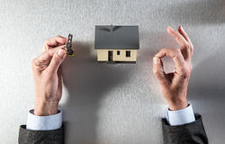 Hyra, sälja eller köpa hem med tangent i avkopplade händer Fotografering för Bildbyråer
