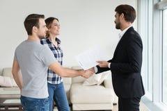 Hyresgäster för fastighetsmäklare- eller hyresvärdhandshakingpar gör fastighetavtal fotografering för bildbyråer