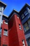 Hyreshus med röd tegelsten och blå himmel royaltyfri bild