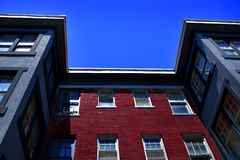 Hyreshus med röd tegelsten och blå himmel fotografering för bildbyråer