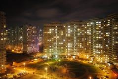 Hyreshus på aftontid med ljus i fönster på fasad Fotografering för Bildbyråer