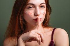 Hyssja ner gestkvinnaöverkanten - hemlig fokuserad stirrande royaltyfri foto