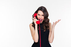 Hysterical aggressive young female shouting and talking on red telephone Royalty Free Stock Image