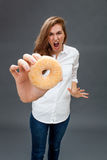 Hysterical beautiful young woman screaming against a fat donut. Furious beautiful young woman acting hysterical, screaming at a fat donut as stressful emphasis Royalty Free Stock Photos