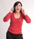 Hysterical brunette talking with two phones Royalty Free Stock Photos