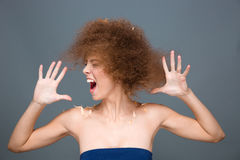 Hysterical excited curly woman sreaming and shaking her head Royalty Free Stock Images
