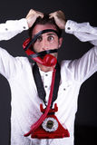 A hysterical telephoneman. A hysterical man with the phone tied to the face Stock Image