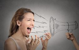 Hysterical woman shouting against someones megaphone. Portrait angry hysterical woman shouting against someones loud megaphone  grey wall background. Negative Royalty Free Stock Photography