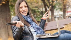 Hysterisches Mädchen mit zu vielen Schirmen, mobils, Tabletten und lapto Stockbild