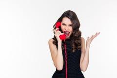 Hysterisk aggressiv ung kvinnlig som ropar och talar på den röda telefonen Royaltyfri Bild