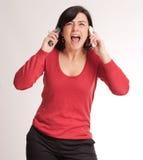 Hysterisk brunett som talar med två telefoner Royaltyfria Foton