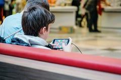 Iéna, Allemagne 23 mars 2019 Adolescent jouant le jeu sur Internet sur le téléphone portable ou le smartphone au centre commercia image stock