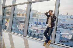 Iść być domowy wkrótce Portret przystojnego młodego człowieka roześmiany mówienie na telefonie podczas gdy czekający jego lot prz Obrazy Stock