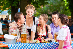I ölträdgården - vänner på en tabell med öl Arkivbild