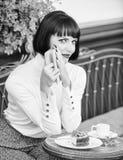 i 妇女安排饮料喜欢读好书咖啡馆大阳台 女性的现代文学 ?? 免版税库存照片
