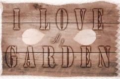 措辞I爱书面的我的庭院,在木棕色背景的被烧的信件 免版税图库摄影