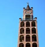 I abstrakt och kyrkligt torn för castellanza sätta en klocka på den soliga dagen Arkivfoton
