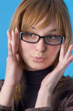 I accept these glasses?. The girl on a blue background tries on glasses Royalty Free Stock Photos